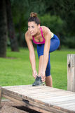 Het glimlachen van donkerbruine sportvrouw bindend kant in park Royalty-vrije Stock Foto's