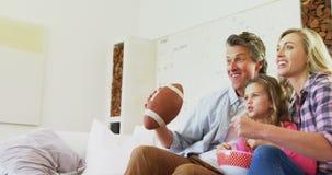 Het glimlachen van familie het letten op televisie terwijl het hebben van popcorn in woonkamer 4k stock footage
