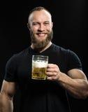 Het glimlachen van Gebaard mens het drinken bier van een biermok over zwarte bac stock foto