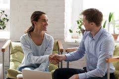 Het glimlachen van gelukkige vrouw het schudden hand van zekere zakenman stock foto's