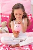 Het glimlachen van het geld van de meisjesbesparing in een piggy-bank Royalty-vrije Stock Foto's