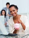 Het glimlachen van het geld van de onderneemsterbesparing in een piggy-bank Stock Afbeelding