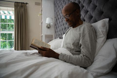Het glimlachen van het hogere boek van de mensenlezing terwijl het ontspannen op bed Royalty-vrije Stock Foto's