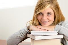 Het glimlachen van het leunende hoofd van de studententiener op boeken Stock Fotografie