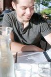 Het glimlachen van het menu van de mensenlezing in restaurant Stock Foto