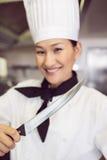Het glimlachen van het vrouwelijke mes van de kokholding in keuken Royalty-vrije Stock Foto