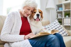 Het glimlachen van het hogere boek van de vrouwenlezing met hond stock fotografie