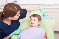 Het glimlachen van jong geitje in tandartsbureau met vriendschappelijke vrouw arts Stock Foto