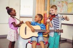 Het glimlachen van jonge geitjes die gitaar, viool, fluit in klaslokaal spelen royalty-vrije stock fotografie