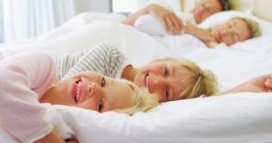 Het glimlachen van jonge geitjes die op bed ontspannen terwijl ouders die op achtergrond 4k slapen stock video