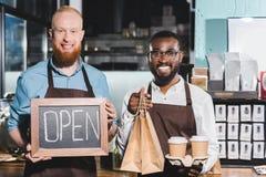 het glimlachen van jonge multi-etnische eigenaars van koffiewinkel met koffie vormt document zakken en bord met het van letters v stock foto's