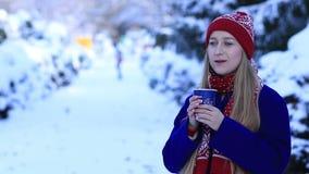 Het glimlachen van jonge vrouw het drinken koffie in de koude winter stock footage