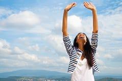 Het glimlachen van jonge vrouw opgeheven handen aan hemel stock foto
