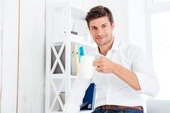 Het glimlachen van jonge zakenman het drinken kop thee in het bureau royalty-vrije stock fotografie