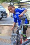 Het glimlachen van jongen het bevestigen fiets op stoep in stadsstraat, Iran Royalty-vrije Stock Foto's