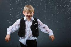 Het glimlachen van jongenstribunes in regen Stock Foto's