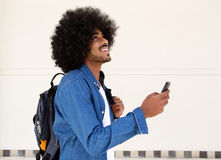 Het glimlachen van kerel die met cellphone en zak lopen Royalty-vrije Stock Afbeelding