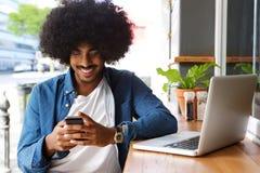 Het glimlachen van kerel die mobiele telefoon en laptop met behulp van Stock Afbeeldingen