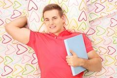 Het glimlachen van kerel die op een bed liggen en het houden van een boek Royalty-vrije Stock Foto