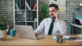 Het glimlachen van kerel die op mobiele telefoon spreken en op laptop in modern bureau typen stock videobeelden