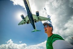 Het glimlachen van kerel die selfie met vliegtuig nemen die over op beroemd Maho-strand vliegen Concept vakantie en het reizen royalty-vrije stock afbeeldingen
