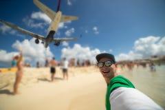 Het glimlachen van kerel die selfie met vliegtuig nemen die over op beroemd Maho-strand vliegen Concept vakantie en het reizen royalty-vrije stock afbeelding