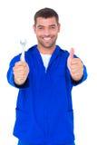 Het glimlachen van mechanische holdingsmoersleutel terwijl het gesturing omhoog beduimelt Royalty-vrije Stock Foto