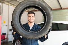 Het glimlachen van Mechanische Looking Through Car-Band in AutoReparatiewerkplaats stock afbeeldingen