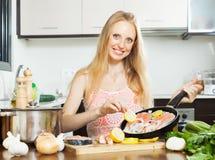Het glimlachen van meisje het koken zalmvissen met citroen Stock Foto