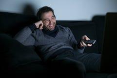 Het glimlachen van mens het letten op televisie bij nacht royalty-vrije stock foto's