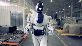 Het glimlachen van menselijk-als robot loopt voorwaarts langs de fabrieksfaciliteit