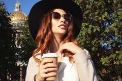 Het glimlachen van modieuze jonge vrouw het drinken koffie terwijl het lopen op een stadsstraat royalty-vrije stock foto's