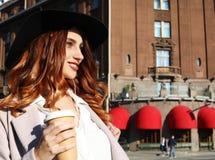 Het glimlachen van modieuze jonge vrouw het drinken koffie terwijl het lopen op een stadsstraat royalty-vrije stock fotografie