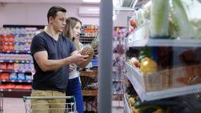 Het glimlachen van paar het plukken ananas in een supermarkt stock video