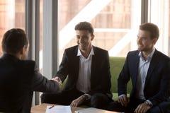 Het glimlachen van partnershanddruk die succesvolle overeenkomst ondertekenen royalty-vrije stock foto's