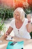 Het glimlachen van rijpe vrouw het drinken koffie in de koffie Omslag en ph royalty-vrije stock foto