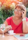 Het glimlachen van rijpe vrouw het drinken koffie in de koffie Omslag en ph stock foto