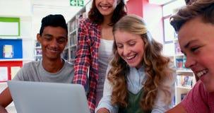 Het glimlachen van schooljonge geitjes gebruikend laptop in bibliotheek stock videobeelden