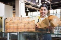 Het glimlachen van server in schort die een brood aanbieden stock foto's