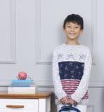 Het glimlachen van tiener Aziatische het boekzak die van de jongensholding zich naast bureau bevinden Stock Foto's