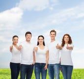 Het glimlachen van tieners in t-shirts het tonen beduimelt omhoog Stock Fotografie