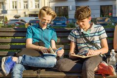 Het glimlachen van twee schooljongens die boeken lezen die op bank in stad zitten royalty-vrije stock foto's
