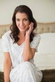 Het glimlachen van vrij bruine haired vrouwenzitting op een bed Royalty-vrije Stock Afbeeldingen