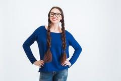 Het glimlachen van vrij jonge vrouw met twee lange vlechten in glazen Stock Afbeeldingen