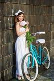 Het glimlachen van vrij het vrouwelijke stellen dichtbij donkere houten muur met pioenen en blauwe fiets Royalty-vrije Stock Foto's