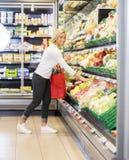 Het glimlachen van Vrouw het Kopen Kool in Supermarkt Stock Afbeeldingen