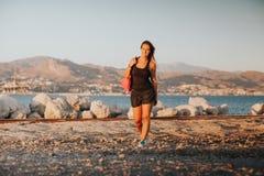 Het glimlachen van vrouw het lopen op zee kust met sportenkleren stock fotografie