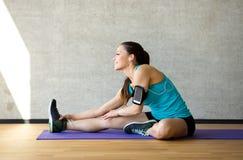 Het glimlachen van vrouw het uitrekken zich been op mat in gymnastiek Stock Foto's