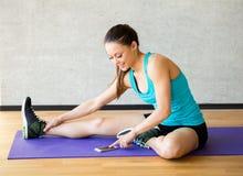 Het glimlachen van vrouw het uitrekken zich been op mat in gymnastiek Stock Afbeelding