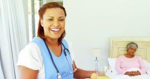 Het glimlachen van vrouwelijk artsen dienend ontbijt aan hogere vrouw op bed 4k stock footage